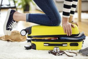 旅行先の荷物トラブル解消法_スーツケースに乗る女性