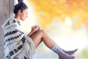 体を温める方法をとる女性